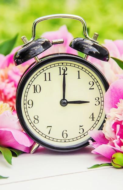 Lentebloemen en wekker. verander de tijd. Premium Foto