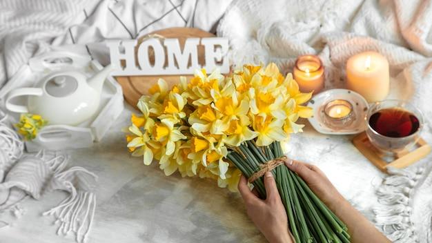 Lentestilleven met een kopje thee en bloemen. lichte achtergrond, bloeiend en gezellig huis. Gratis Foto