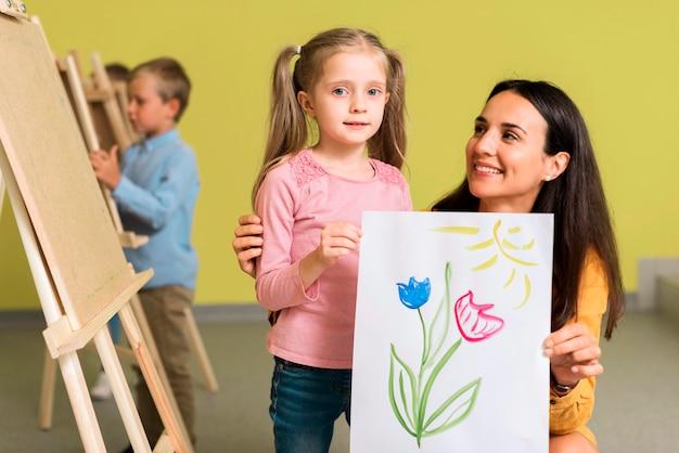 Leraar die de mooie tekening van haar student toont Gratis Foto