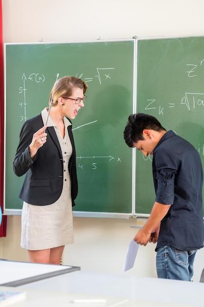 Leraar die een leerling in schoolklasse kritiseert Premium Foto