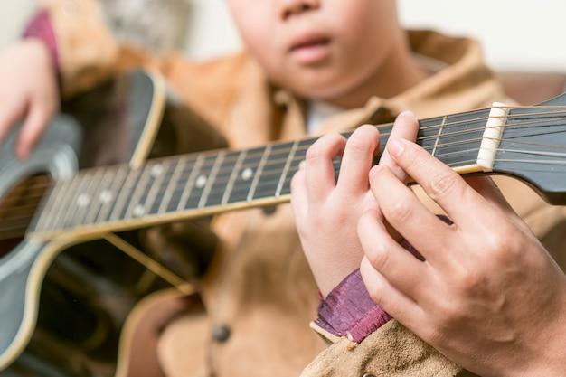 Leraar die gitaarlessen geeft aan leerling in een klaslokaal Premium Foto