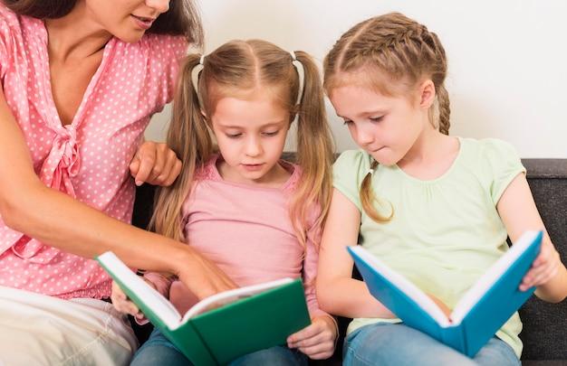 Leraar die haar studenten helpt lezen Gratis Foto