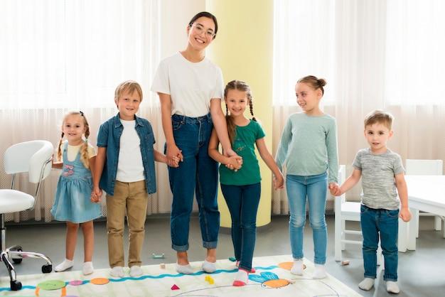 Leraar en kinderen samen poseren Gratis Foto