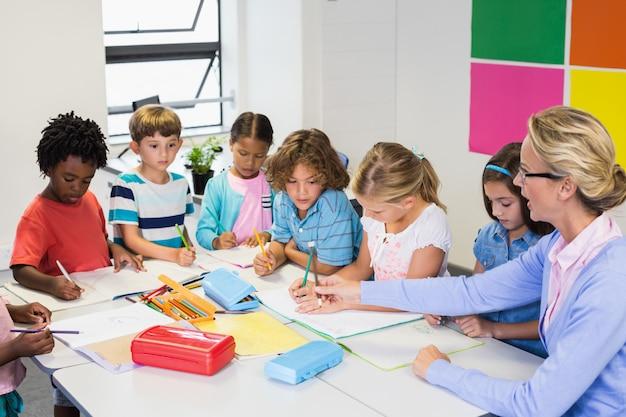 Leraar helpt kinderen met hun huiswerk in de klas Premium Foto