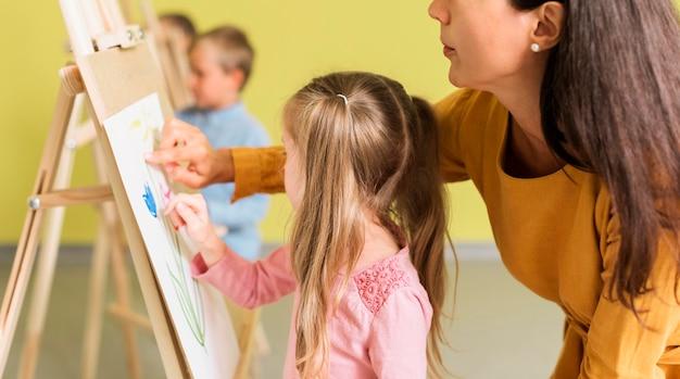 Leraar helpt meisje bij het opstellen van klasse Gratis Foto