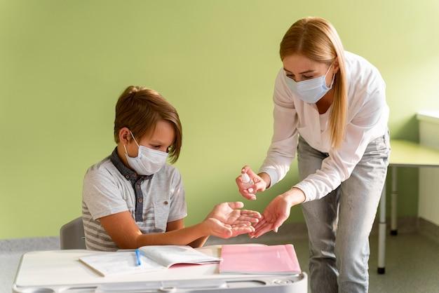 Leraar met medische masker handen van het kind desinfecteren in de klas Gratis Foto