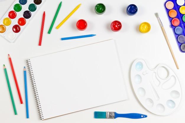Leren, hobby, kunstachtergrond. leeg schetsboek met kunstbenodigdheden eromheen. mockup. bovenaanzicht, plat gelegd Premium Foto