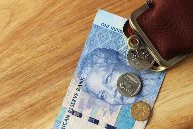 Leren portemonnee en wat kleingeld en een bankbiljet op een houten oppervlak Gratis Foto