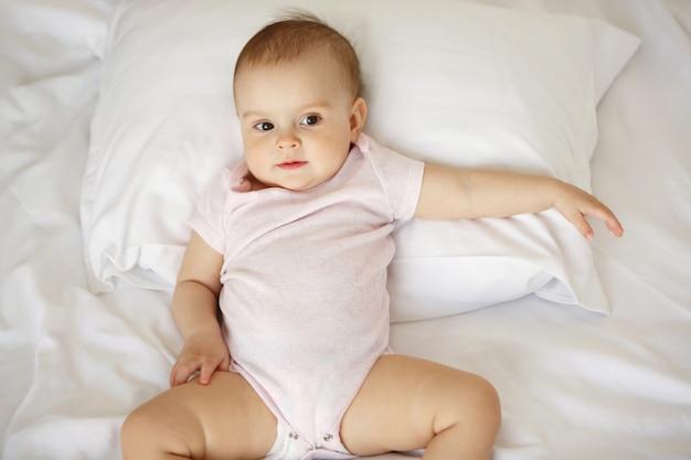 Leuk aardig portret van weinig babyvrouw die op hoofdkussen in bed liggen. van boven. Gratis Foto