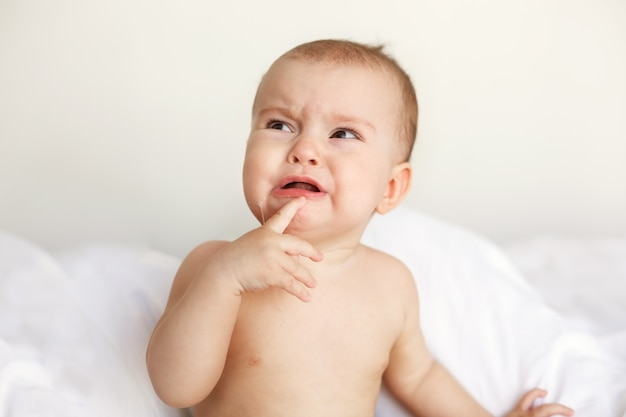 Leuk aardig weinig babyvrouw schreeuwen die thuis met haar mamma op bed liggen. Gratis Foto