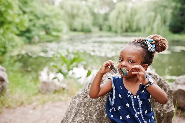 Leuk afrikaans amerikaans babymeisje bij zonnebril Premium Foto