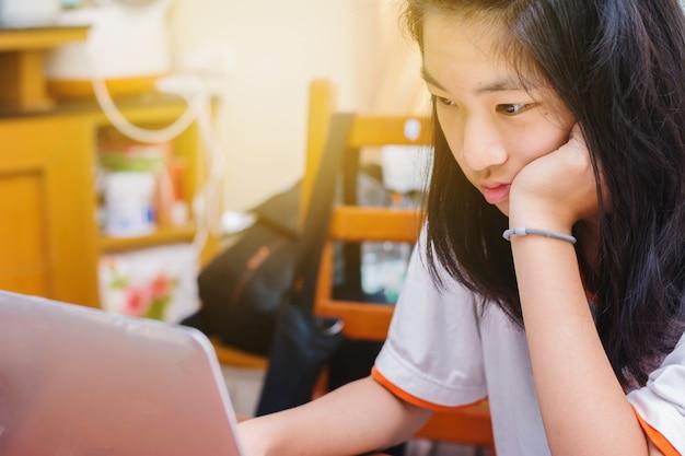 Leuk aziatisch jong meisje die thuiswerk met laptop thuis doen Premium Foto