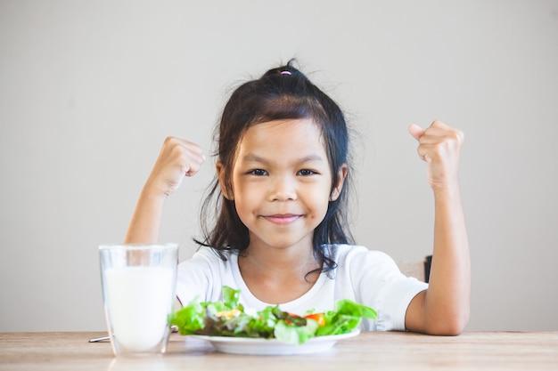 Leuk aziatisch kindmeisje die gezonde groenten en melk voor haar maaltijd eten Premium Foto