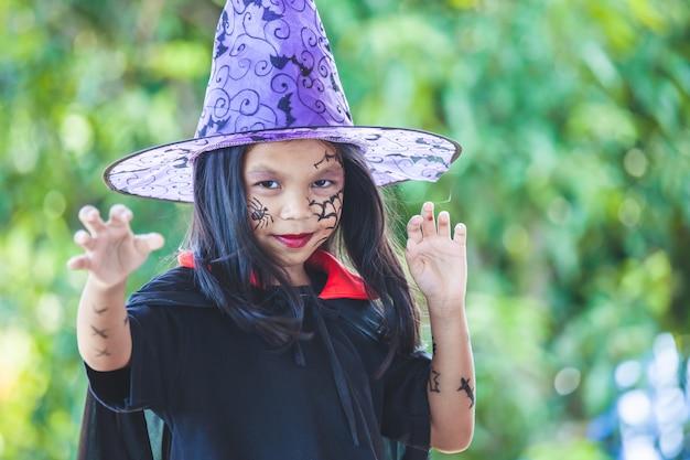 Leuk aziatisch kindmeisje die halloween-kostuums en make-up dragen die pret op halloween-viering hebben Premium Foto
