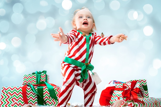 Leuk babymeisje 1 éénjarigen die santahoed dragen die tijdens kerstmis stellen Gratis Foto