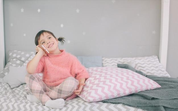 Leuk babymeisje dat een slimme telefoon speelt, smartphone heeft een negatieve invloed op de ontwikkeling en geestelijke gezondheid van uw kind Premium Foto