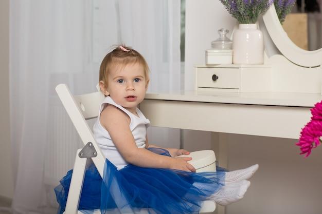 Leuk babymeisje die op haar gedachtengang in een witte slaapkamer met een ronde spiegel letten Premium Foto