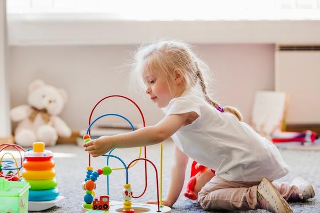 Leuk blond meisje spelen op de vloer Premium Foto