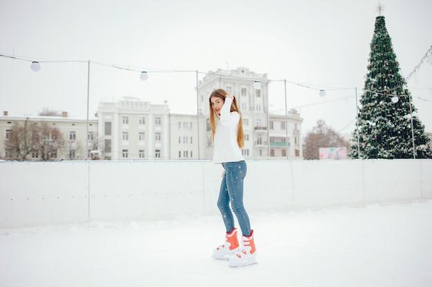 Leuk en mooi meisje in een witte trui in een winterstad Gratis Foto