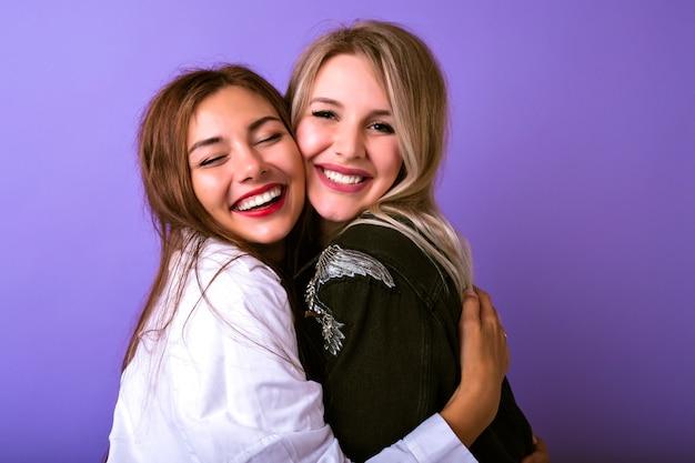 Leuk familieportret van de omhelzingen en de glimlach van twee zustervrouwen, levensstijl die portret, trendy hipsteroutfits, relatiesconcept, natuurlijke schoonheid, gelukkig samen bestuderen. Gratis Foto