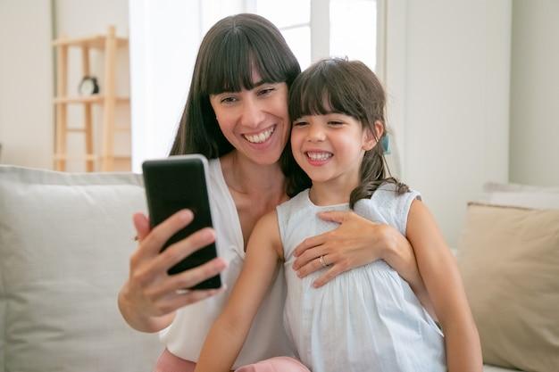 Leuk gelukkig meisje en haar moeder met behulp van telefoon voor videogesprek zittend op de bank thuis samen Gratis Foto