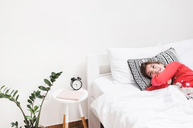 Leuk glimlachend meisje die op bed in de slaapkamer liggen foto