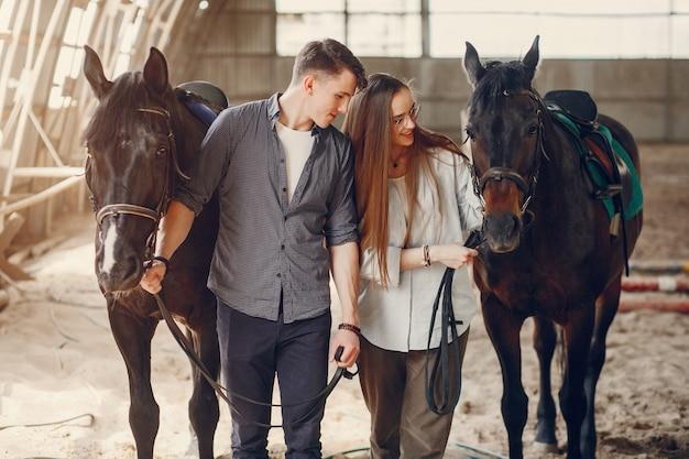 Leuk houdend van paar met paard op boerderij Gratis Foto