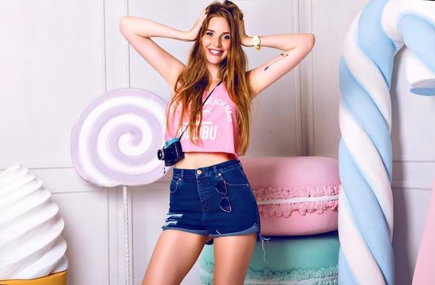 Leuk indoor portret van jonge mooie vrouw in de buurt van enorme kleurrijke rekwisieten snoep. glimlachend, hand in de buurt van gezicht. meisje met roze zomer hemd en blauwe korte broek Gratis Foto