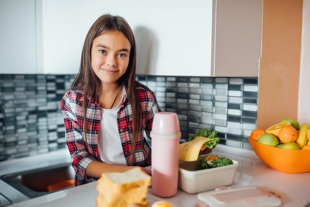 Leuk jong meisje glimlacht en houdt haar gezonde sandwich over haar lunchdoos Premium Foto