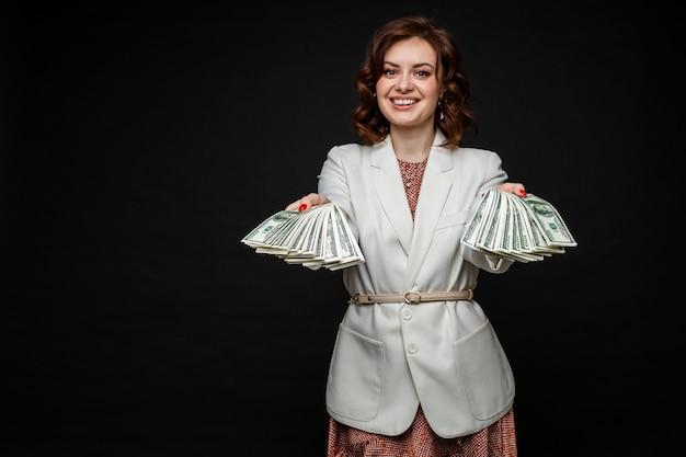 Leuk jong meisje toont veel geld in de handen, foto geïsoleerd op zwarte ruimte Gratis Foto