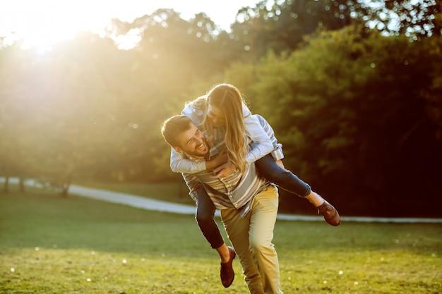 Leuk kaukasisch paar in liefde die op de rug heeft en pret in aard heeft. Premium Foto