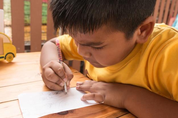 Leuk kind aziatische kleine jongen die thuiswerk op lijst doet Premium Foto