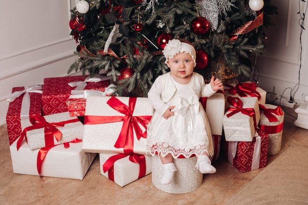 Leuk kind in het witte kleding stellen onder kerstmisboom. Premium Foto