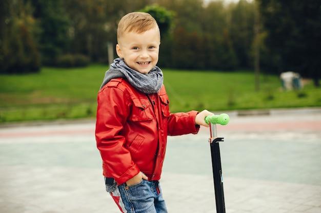 Leuk kind in park het spelen op een gras Gratis Foto