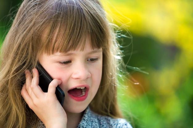Leuk kind jong meisje dat op cellphone in openlucht spreekt. kinderen en moderne technologie, communicatie. Premium Foto