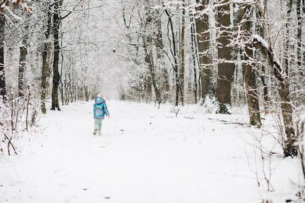 Leuk kindmeisje in een kleurrijke kleding die in een sneeuwwinterpark loopt Premium Foto