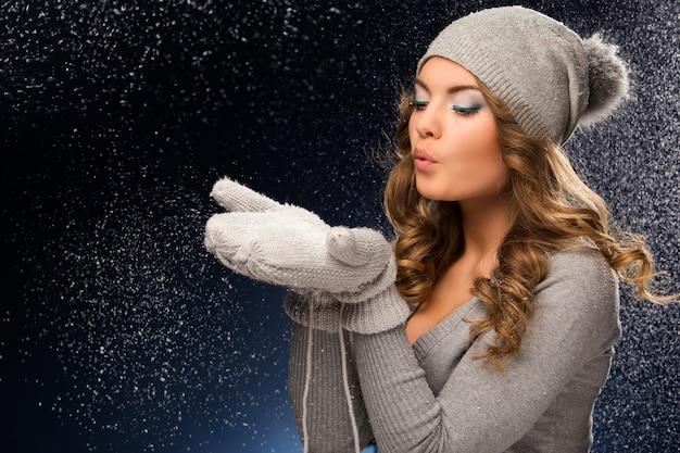 Leuk krullend meisje dat vuisthandschoenen draagt tijdens sneeuwval Gratis Foto
