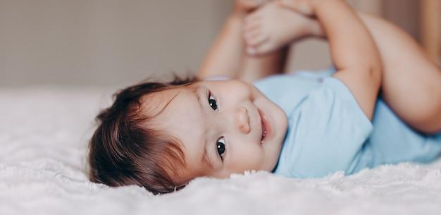 Leuk lachend één éénjarigemeisje dat op bed ligt Premium Foto