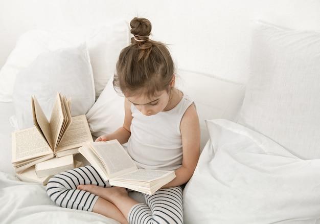 Leuk meisje dat een boek op het bed in de slaapkamer leest. Gratis Foto