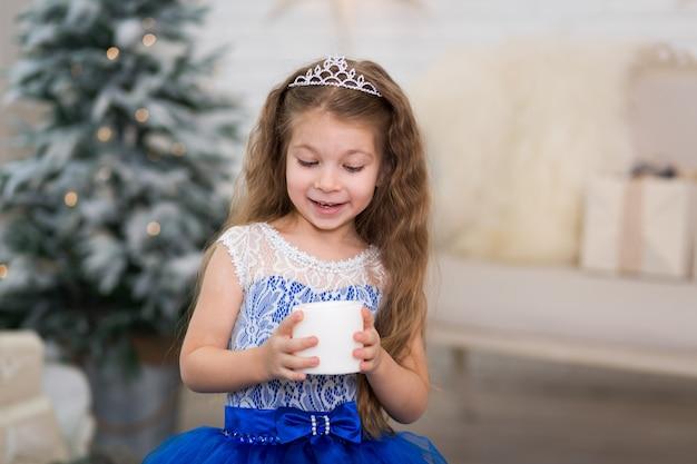 Leuk meisje dat een kunstmatige kaars in haar handen voor huisdecoratie houdt voor de kerstmisvakantie. kindvriendelijk landschap. Premium Foto