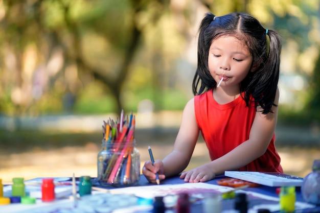 Leuk meisje dat in speelplaats leert. Premium Foto