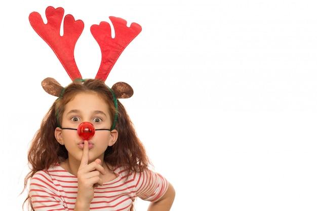 Leuk meisje dat kerstmisgeweitakken en rode neus draagt Premium Foto