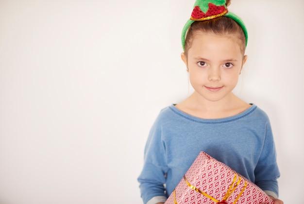 Leuk meisje dat kostuumelf met kerstcadeau draagt Gratis Foto