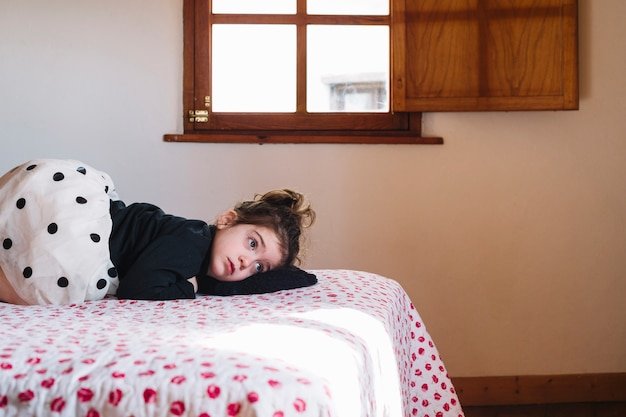 Leuk meisje dat op bed in slaapkamer ligt foto gratis download