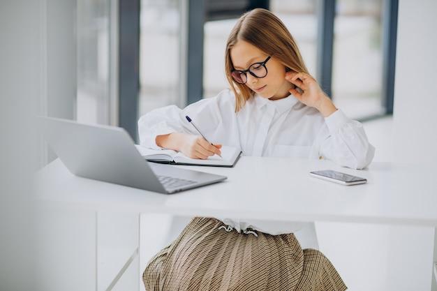 Leuk meisje dat thuis op de computer studeert Gratis Foto