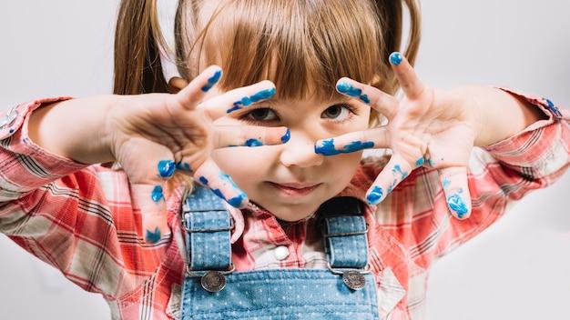 Leuk meisje dat zich met geschilderde vingers bevindt Gratis Foto