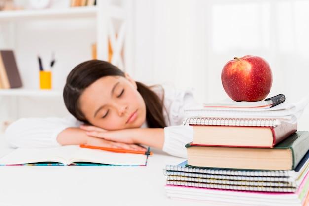 Leuk meisje die dichtbij boeken slapen Gratis Foto