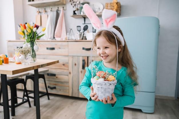 Leuk meisje die in konijntjesoren mand met paaseieren houden Gratis Foto