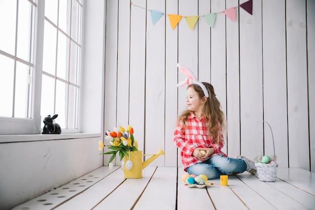 Leuk meisje die in konijntjesoren op vloer met gekleurde eieren zitten Gratis Foto