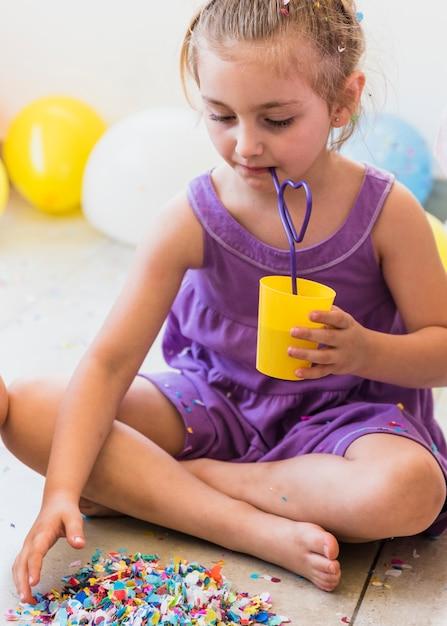 Leuk meisje die sap met stro drinken die confettien op vloer verzamelen Gratis Foto